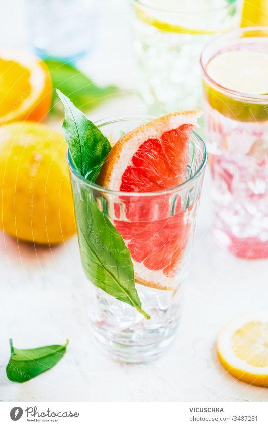 Sommer-Erfrischungsgetränk mit Grapefruitscheiben und grünen Blättern im Sonnenlicht auf weißem Tisch , Nahaufnahme. Aufgegossenes Entgiftungswasser. Vitamin C. Antioxidans