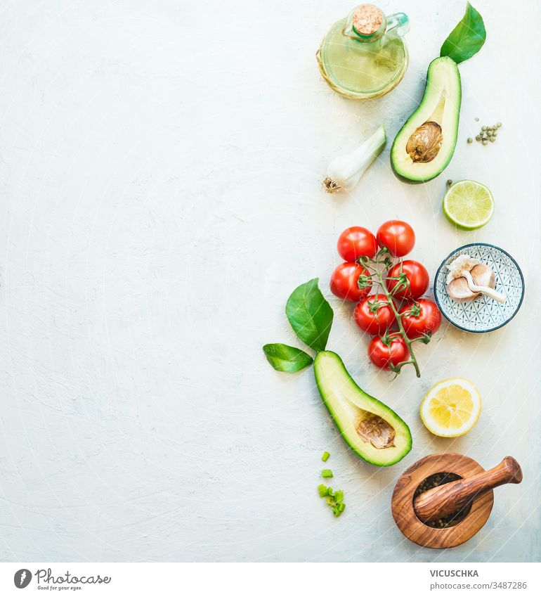 Lebensmittelhintergrund mit frischen Salatzutaten: Avocado, Tomaten, Zitrone, Knoblauch und Olivenöl zur schmackhaften Salatzubereitung, Draufsicht. Gesundes Essen.  Vegetarisches Mittagessen oder Snack. Grenze