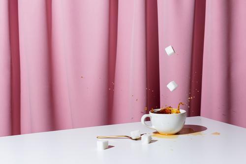 Tasse Tee oder Kaffee auf weißem Tisch vor rosa Draperie, selektiver Fokus Koffein schwarz Espresso Aroma Morgen Getränk Gardine Vorhang trinken Hand
