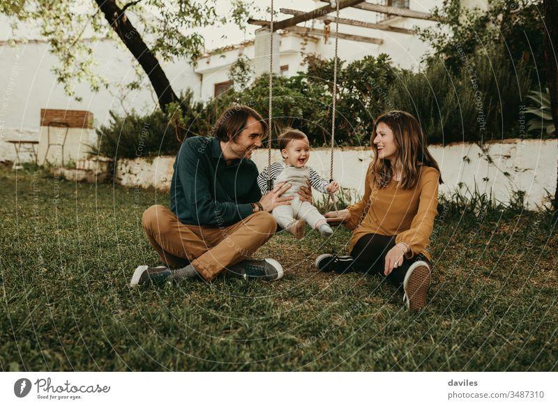 Vater und Mutter schaukeln ihr Baby, das auf dem grünen Gras im Park sitzt. Das Kind lacht glücklich. Aufregung Genuss Lächeln Sitzen Pflege unschuldig Liebe