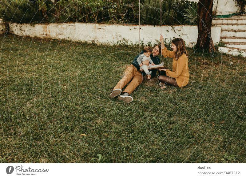 Schönes Paar genießt mit seinem kleinen Sohn auf einer Schaukel auf dem grünen Rasen des Gartens auf dem Land Aufregung Genuss Lächeln Sitzen Pflege unschuldig