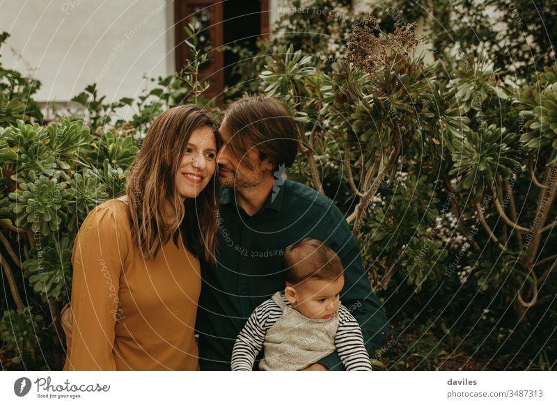 Liebenswertes Paar steht zusammen, während der Mann ihren kleinen Sohn hält alternativ Indie Hipster Lächeln Frau Papa Eltern Porträt im Freien Garten