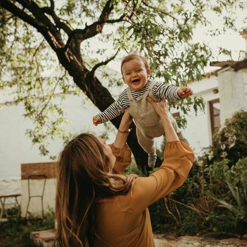 Mutter hält ihren kleinen Sohn in die Luft und das Baby lacht. Spielen Erwachsener Fliege Waffen Werfen genießend Elternschaft blond Garten Baum Leben Frau