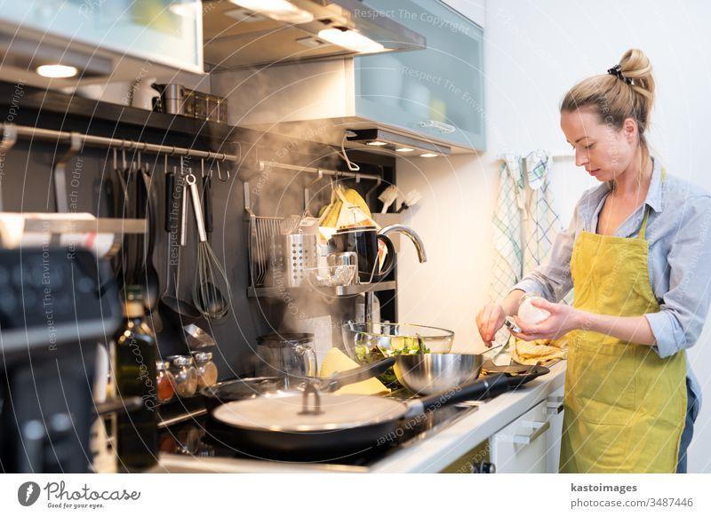 Bleiben Sie zu Hause Hausfrau Frau kocht in der Küche, Salzen Gericht in einem Kochtopf, Zubereitung von Speisen für die Familie Abendessen. heimwärts