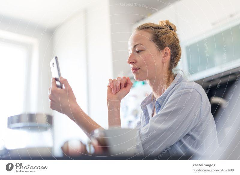 Junge, zufriedene Frau, die zu Hause in der heimischen Küche sitzt und Social-Media-Apps auf dem Mobiltelefon nutzt, um mit ihren Lieben zu chatten und zu stylen. Zu Hause bleiben, sozial distanzierender Lebensstil.