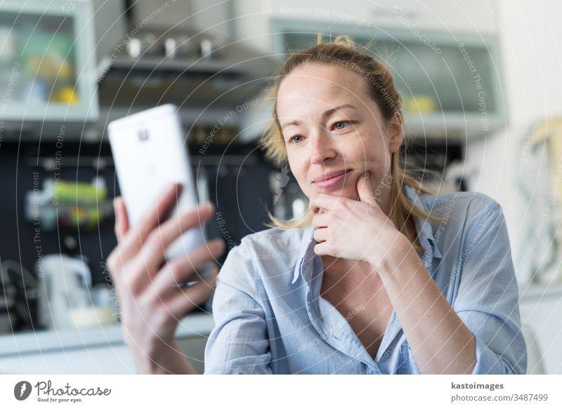 Junge, lächelnde, fröhliche, zufriedene Frau, die zu Hause in der Küche sitzt und Social-Media-Apps auf dem Handy zum Chatten und Stylen mit ihren Lieben nutzt. Bleiben Sie zu Hause, sozialer distanzierender Lebensstil.
