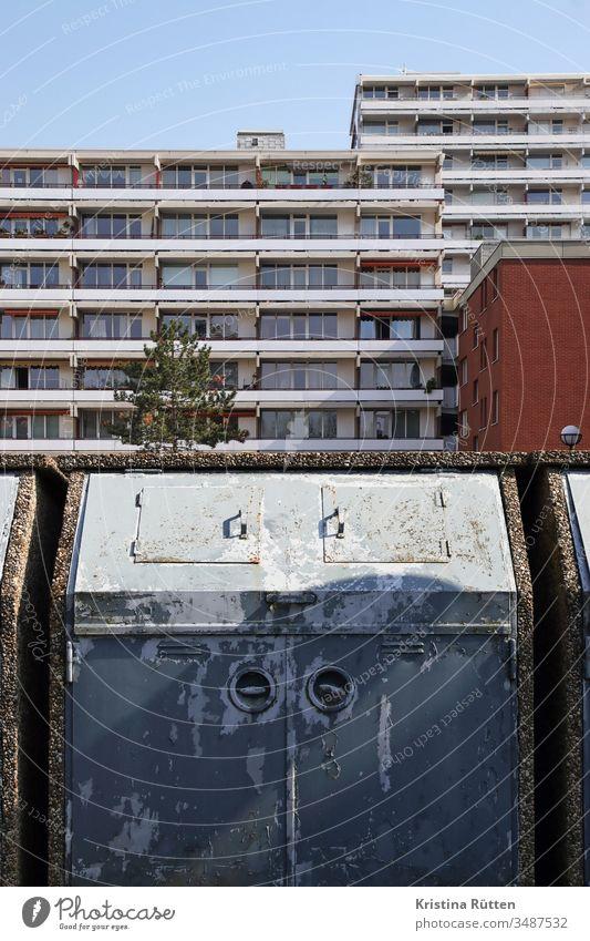 müllcontainer und wohnblock mülltonne mülleimer müllentsorgung mehrfamilienhaus mehrfamilienhäuser wohnsiedlung hochhaus hochhäuser gebäude fassade balkone