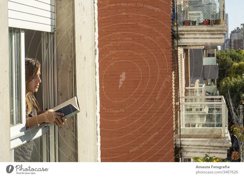 Frau in den Fenstern während der Quarantäne beim Lesen eines Buches Appartement schön blind Windstille Teppich Stuhl Komfort bequem Corona-Virus Bund 19