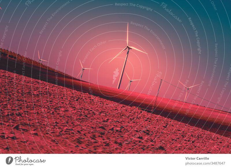 Eine elektrische Windmühlenturbine in einem farbenfrohen Sonnenuntergang und Landschaft Energie Kraft Turbine Elektrizität Himmel Umwelt Bauernhof alternativ
