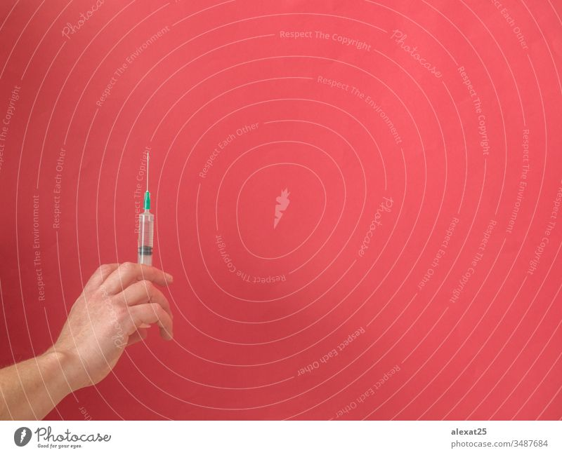 Hand mit Spritze auf rotem Hintergrund mit Kopierfeld Antibiotikum Textfreiraum Coronavirus covid-19 Krankheit Dosis Medikament Seuche Gerät Gesundheit