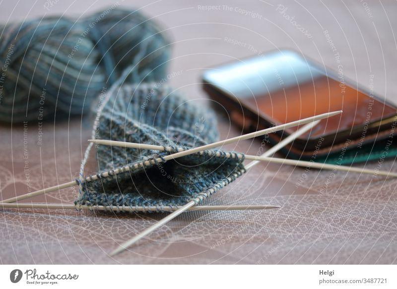 Strickzeug für Socken liegt auf dem Tisch, daneben ein Smartphone Wolle Stricknadel Wollknäuel Freizeit & Hobby Handarbeit Strickmuster Wärme weich stricken
