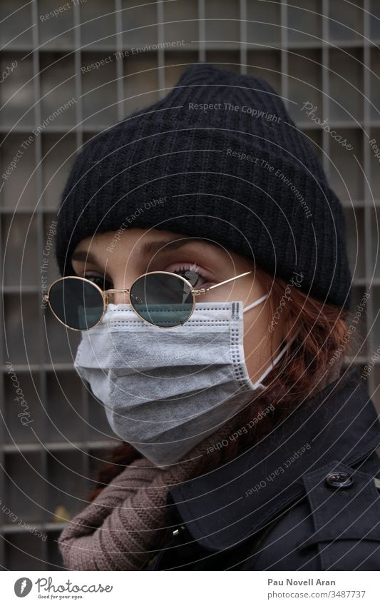 Nahaufnahme einer Frau, die ihr Gesicht mit einer Schutzmaske bedeckt. Virus-Konzept medizinische Ausrüstung Gesichtsmaske Seuche Coronavirus schützend