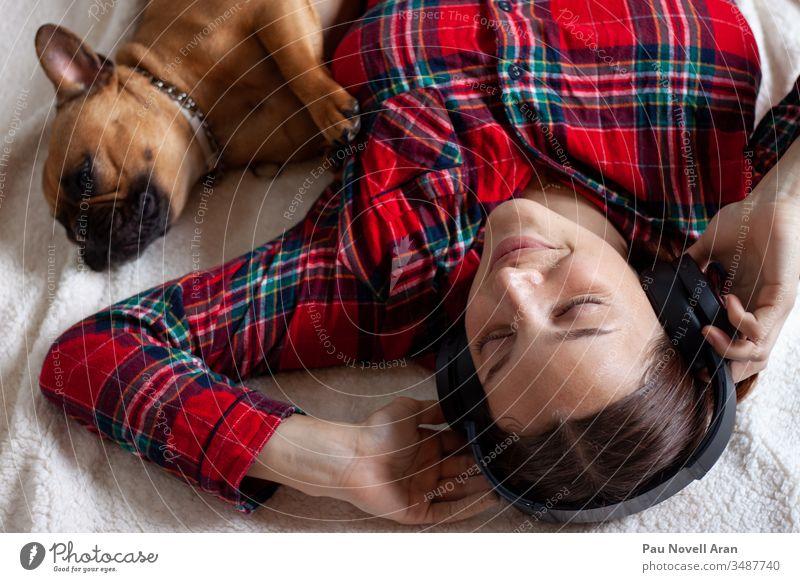 Französische Bulldogge mit junger Frau mit Kopfhörern, die lächelnd auf der Couch liegt französische Bulldogge Hund LAZY Klang Vorstellungskraft Menschen Raum
