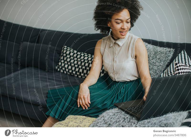 Junge schöne Dame mit lockigem Haar arbeitet am Notebook, während sie zu Hause auf der Couch sitzt jung Laptop Computer Frau Sofa heimwärts Person arbeiten