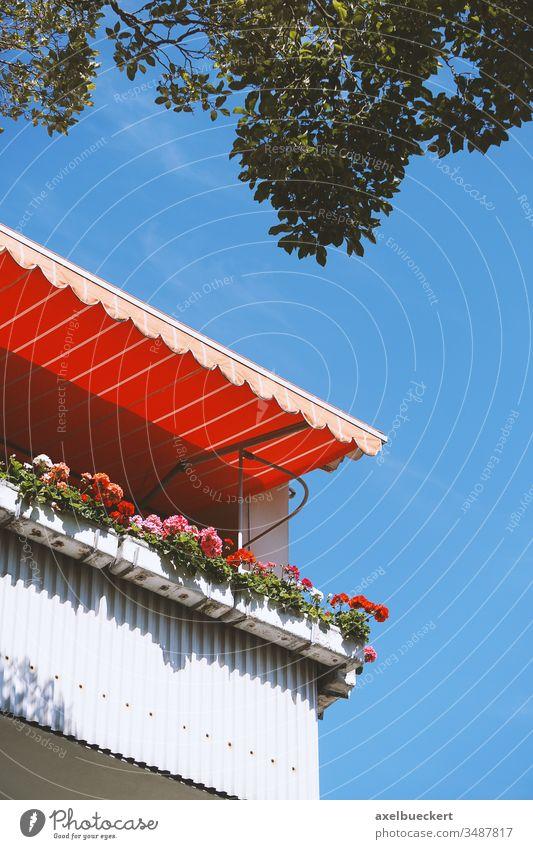 Balkonien - Balkon mit Geranien in Blumenkästen und Markise balkonien zuhause bleiben urlaub auf balkonien Urlaub zuhause typisch deutsch zu Hause bleiben