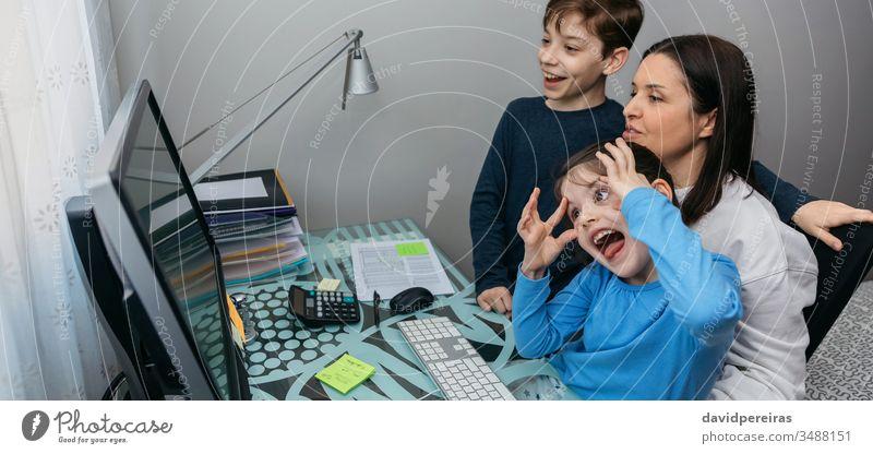 Familie spricht per Videoanruf, während das Mädchen eine Grimasse zieht Mutter Kinder Spaß Grimassen schneiden Computer Coronavirus Quarantäne sprechend