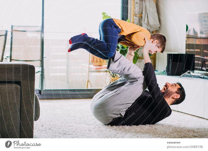 Vater und Sohn spielen zu Hause bezaubernd Air Baby Bonden Junge aufrichtiges Lachen Kind Spaß bei der Kinderbetreuung Kindheit Coronavirus covid-19 Papa