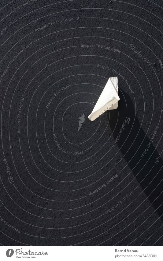 Kleines Etwas Papier Schnipsel Schatten Licht Schwarzweißfoto Wind Wand Haus kleben Etikett Fundstück Detailaufnahme Mauer Kontrast Tag rau struktur Putz