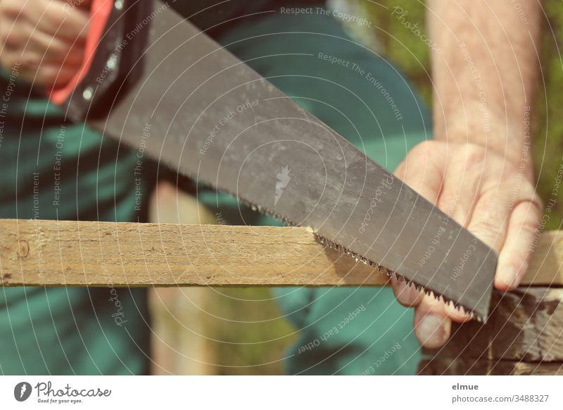 Mann sägt mit Fuchsschwanz eine Holzlatte durch - Ausschnitt Säge Werkzeug Arbeitsschutz sägen Handwerker to it yourself Latte arbeiten Freizeit & Hobby