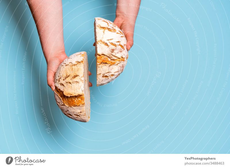 Brot in zwei Scheiben geschnitten und in den Händen einer Frau gehalten. Sauerteig-Brot obere Ansicht backen gebacken Bäckerei Brot backen Blauer Hintergrund