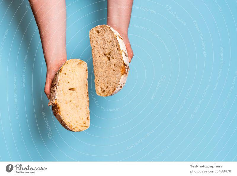 Sauerteigbrot in zwei Scheiben geschnitten vor einem blauen Hintergrund. obere Ansicht backen gebacken Bäckerei Brot backen Blauer Hintergrund Brot im Inneren