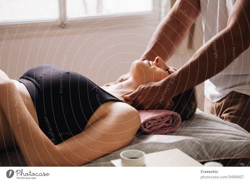 weniger als ein Masseur, der eine Nackenmassage an einer schönen liegenden Frau ausführt alternativ Aromatherapie Arthritis Rücken Wesen Körperpflege Knochen