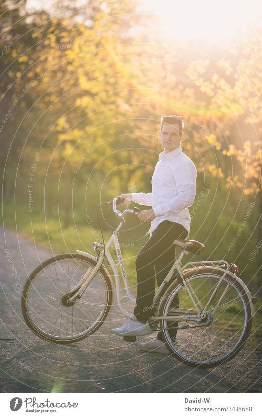 Mann fährt mit dem Fahrrad durch die Natur und macht eine Fahrradtour Fahrradfahren Sonnenlicht Schönes Wetter spass Freude enstpannung Naturliebe Ruhe