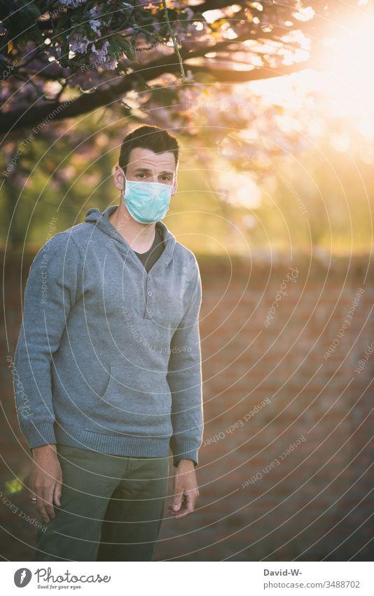 Maskenpflicht Corona Mann mit Mundschutz Atemschutzmaske draußen schaut in Kamera coronavirus Schutzmaske Virus verzweifelt Blick in die Kamera traurig Natur