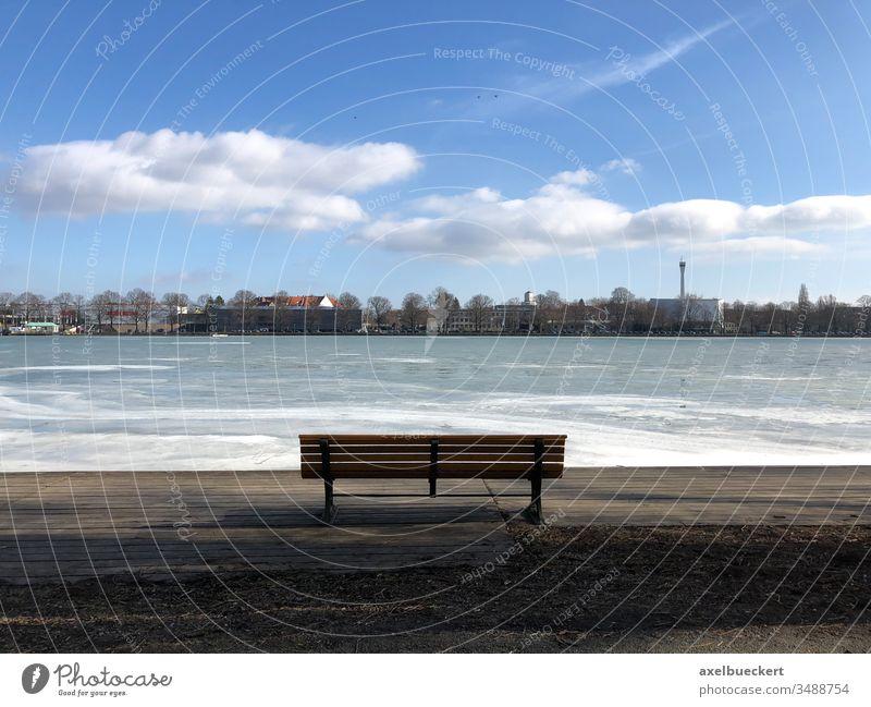 leere Bank mit Blick auf zugefrorenen Maschsee in Hannover Eis See Parkbank Winter Seeufer Aussicht Tag sonnig Kälte Einsamkeit Eisfläche kalt Frost Wasser