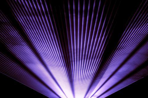 Violette Lasershow-Nachtclubbühne mit funkelnden Strahlen. Luxuriöse Unterhaltung in Nachtclub-Veranstaltung, Festival, Konzert oder Silvester. Strahlenstrahlen sind Symbol für Wissenschaft und Universumsforschung