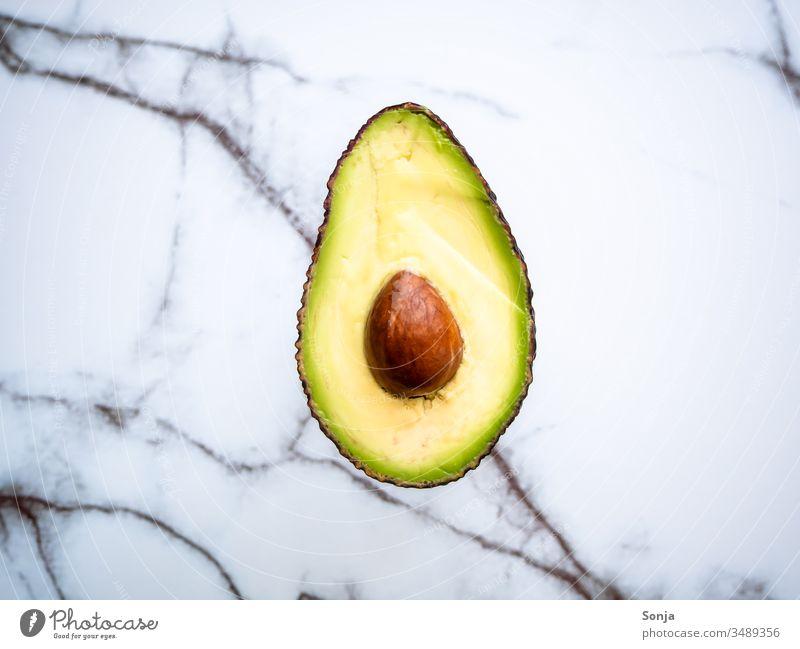 Halbierte Avocado mit Kern auf einem Marmorhintergrund, Draufsicht halbiert Avocadokern draufsicht Lebensmittel Gesunde Ernährung Vegetarische Ernährung frisch