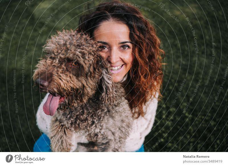 Eine schöne Frau ist mit ihrem Hund auf der Wiese. Die Besitzerin umarmt ihr Haustier, während sie in die Kamera schaut. Sie genießen einen Tag im Park. Das Haustier ist ein spanischer Wasserhund mit braunem Fell.