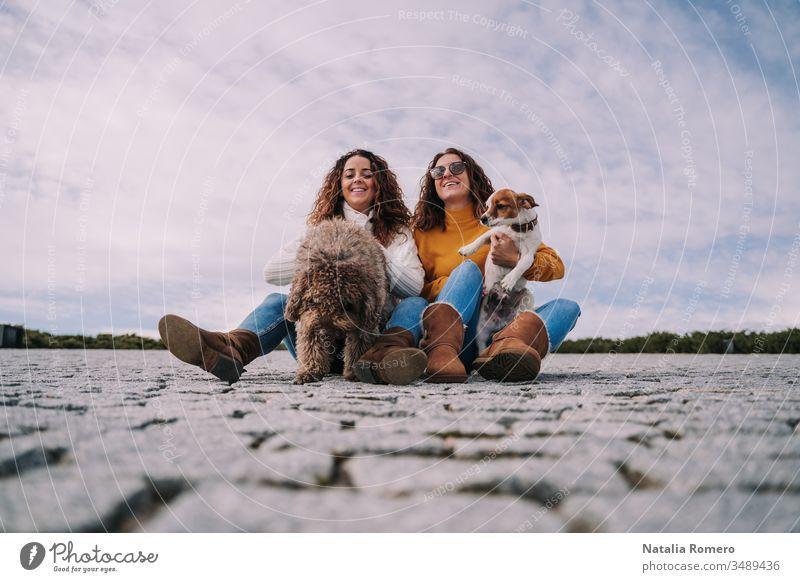 Zwei schöne Frauen sitzen mit ihren Haustieren im Park. Sie spielen und genießen einen gemeinsamen Tag. Es ist ein bewölkter Tag. zwei Hund freundlich Menschen