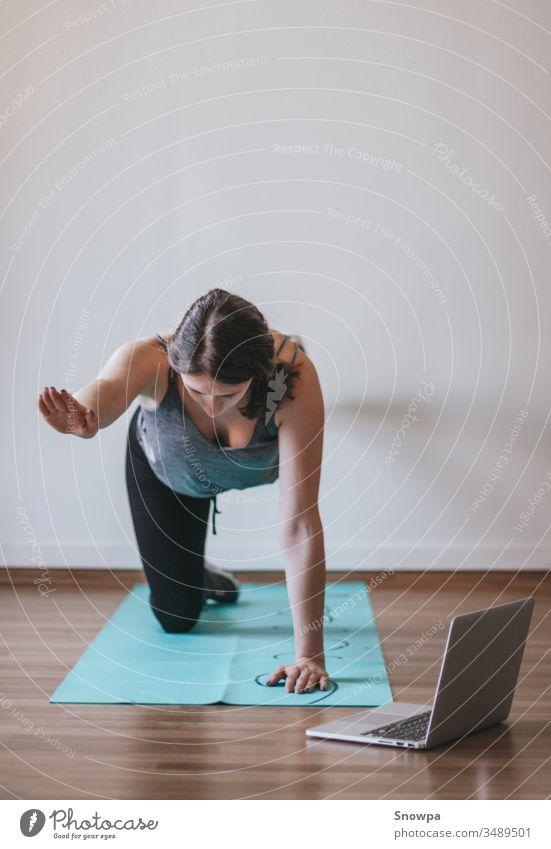 Junge Frau, die zu Hause Online-Yoga macht. Online-Fitness, Heimtraining. aktiv Erwachsener Asana Athlet sportlich attraktiv Hintergrund schön Körper Pflege