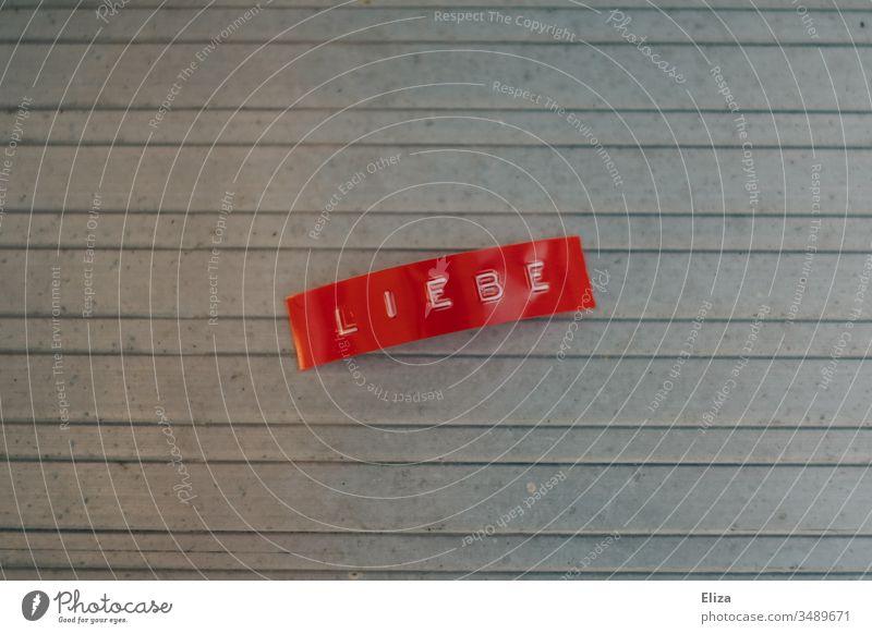 Ein rotes Etikett auf dem das Wort Liebe geschrieben steht Buchstaben Schriftzeichen Menschenleer grau Text Gefühle Hintergrund neutral Metall linien