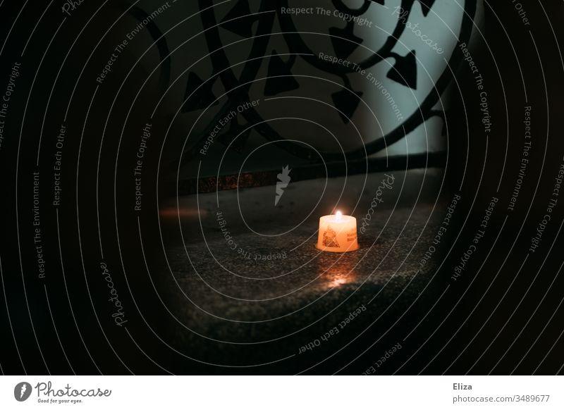 Eine brennende Kerze in der Kirche Tod Gott erinnern Textfreiraum oben Schwache Tiefenschärfe Licht Dunkelheit Spiritualität Gotteshaus Textfreiraum rechts