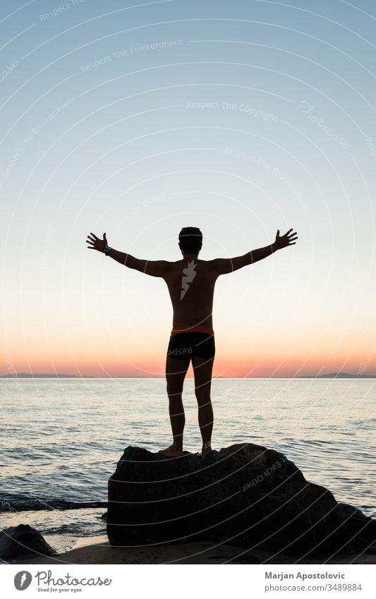 Silhouette eines Mannes, der den Sonnenuntergang am Strand genießt aktiv Abenteuer allein Rücken Schönheit genießend frei Freiheit Typ gutaussehend Fröhlichkeit
