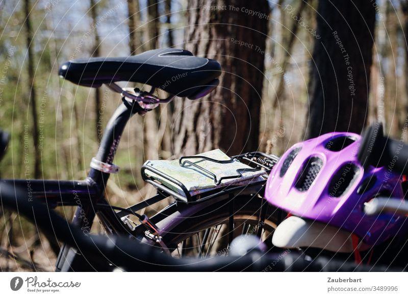 Sattel eines Fahrrads mit Karte und Fahrradhelm bei einer Radtour im Wald Landkarte Gepäckträger Bäume lila Fahrradsattel grün Freizeit & Hobby