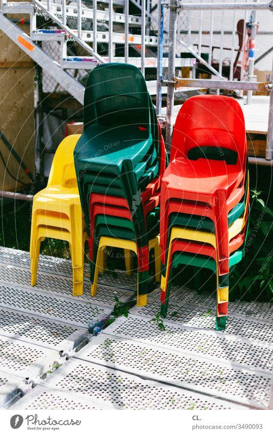 ein stapel bunter stühle Stuhl Stühle Stapel stapelbar draußen Veranstaltung Plastikstuhl Event rot gelb grün Farbfoto Menschenleer Außenaufnahme Tag