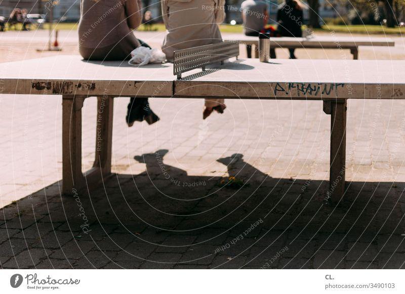 menschen sitzen auf tischtennisplatten Tischtennisplatte Pause Pause machen Spielplatz Mittagspause Park Menschen personen Erholung Außenaufnahme Tag Farbfoto