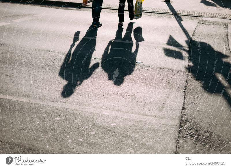 schatten von zwei personen auf der straße Fußgänger gehen Menschen Paar Bewegung Schatten Straße Schattenspiel Spaziergang spazierengehen Einkaufen