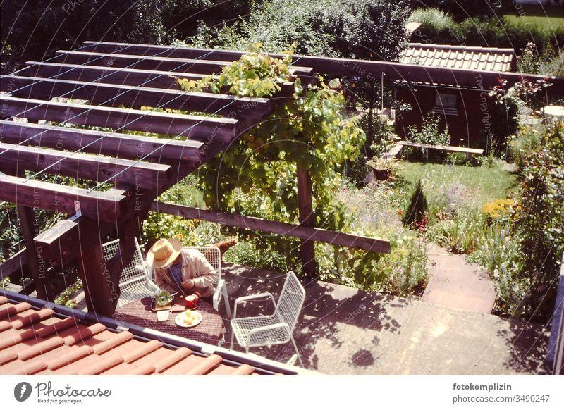 Mann beim Essen auf Terrasse mit Blick von oben Terasse Single allein Witwer Gartenleben Einsamkeit einzeln Mensch einsam terrasse Laube mittagessen Hütte