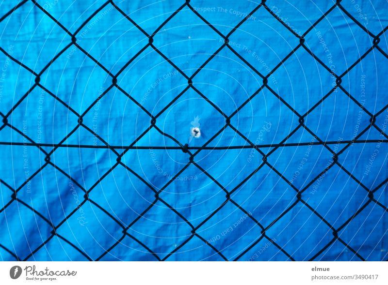Maschendrahtzaun vor blauer PVC-Plane mit kleinem Loch Sichtschutz Schutz Abgrenzung Guckloch Zaun Begrenzung Grenze Drahtzaun Barriere Sicherheit gefangen