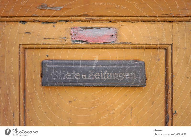 """orange Tür mit Türschlitz """"Briefe und Zeitungen"""" sowie sichtbar entferntes Namensschild Holztür verzogen ausgezogen marode Eingangstür Zwangsräumung abgewohnt"""