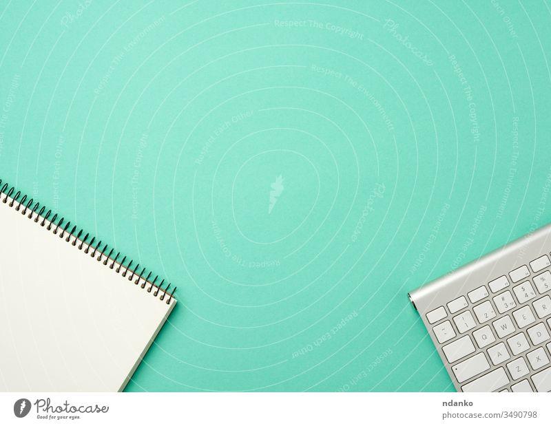 weiße drahtlose Aluminiumtastatur und offenes Notebook mit weißen Blättern auf grünem Hintergrund Keyboard Desktop Technologie Business pc Computer modern