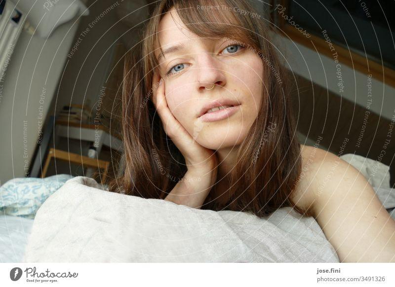 Porträt einer jungen Frau, die morgens im Bett liegt langhaarig Lebensfreude einfach Junge Frau Ponyfrisur Blick in die Kamera hübsch feminin Gesicht schön