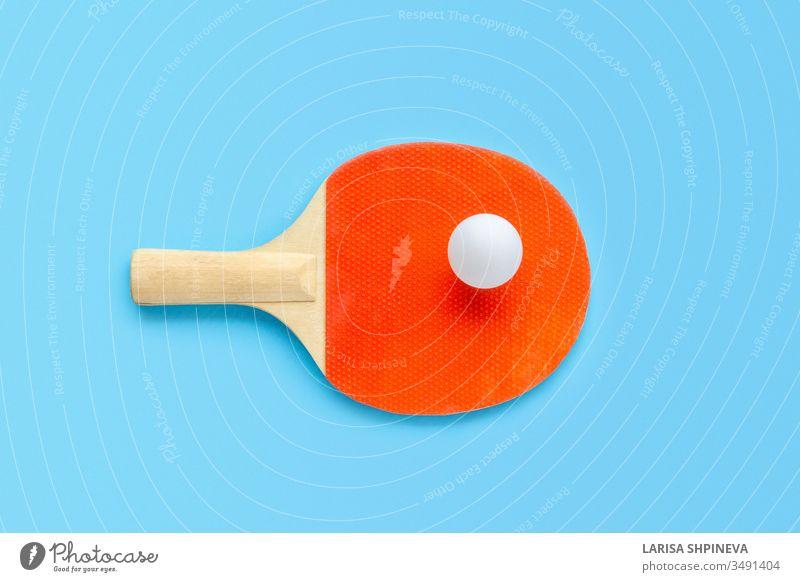Roter Schläger für Tischtennis mit weißem Ball auf blauem Hintergrund. Tischtennis-Sportgerät in minimalem Stil. Flachlegung, Draufsicht, Kopierraum pong Ping
