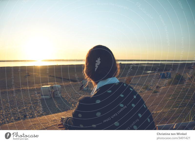 Junge Frau sitzt mit dem Rücken zur Kamera auf der Strandpromenade und schaut über den Strand in den Sonnenuntergang über der Nordsee sitzen Meer Nordseeinsel