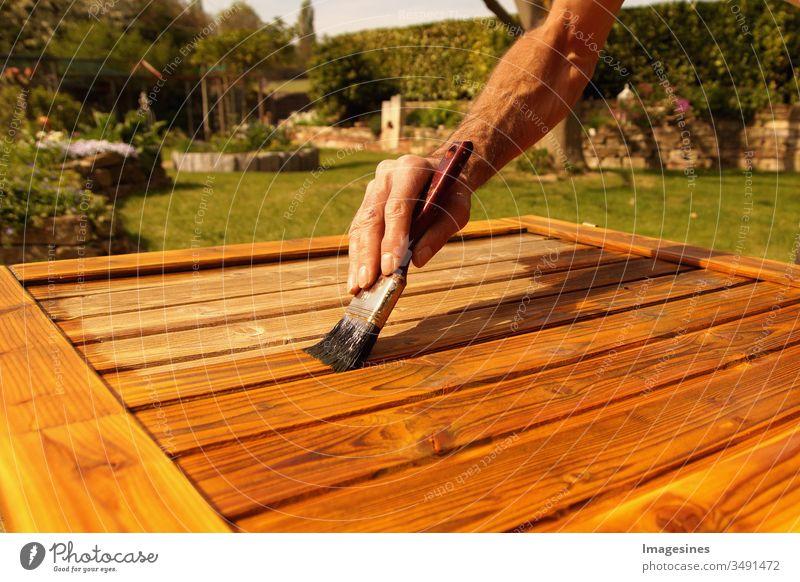 Lasur Streichen Holzarbeiten Draussen im Frühling. Frühjahrsarbeiten. Der Frühling ist gekommen. Männliche Hand mit einem Pinsel. Renovierungsarbeiten, Zimmerei Details mit Holzarbeiten und Handwerker. Zeit draußen zu arbeiten.