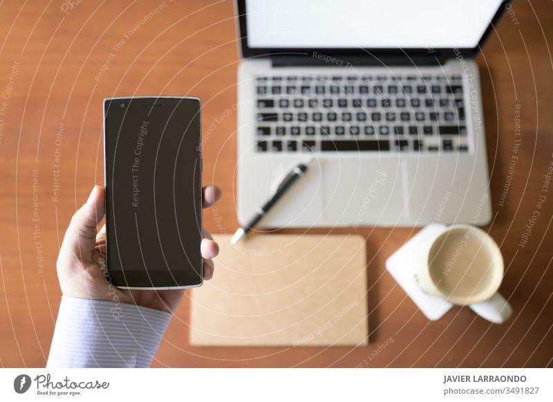 Junger Geschäftsmann hält in der Hand ein Smartphone und in einem unkonzentrierten Hintergrund einen Holzschreibtisch mit einem Laptop, einem Notizbuch und einer Tasse Kaffee.